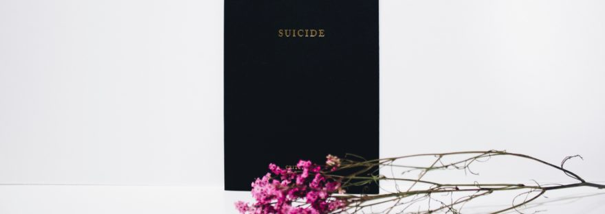 Black suicide book and pink flowers